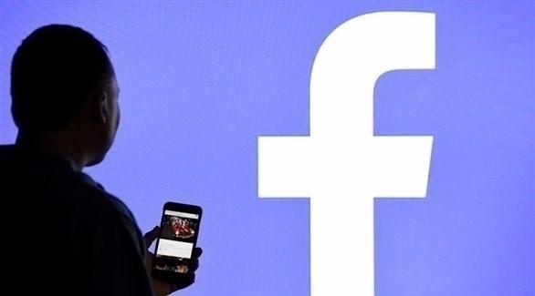 رجل يقف أمام شعار فيس بوك (أرشيف / غيتي)