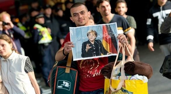 لاجئ يحمل صورة المستشارة الألمانيا أنجيلا ميركل (أرشيف)