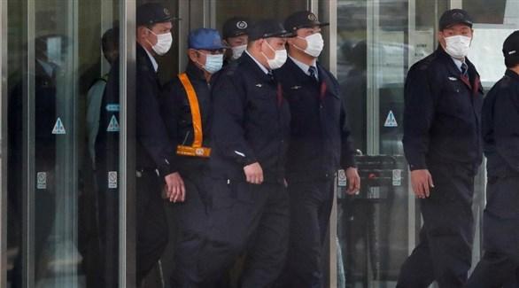كارلوس غصن بالقبعة الزرقاء والحزام البرتقالي مغادراً مركز الاحتجاز في طوكيو (رويترز)