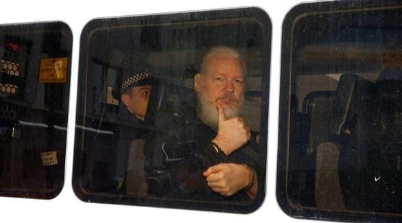 أسانج مقتاداً في حافلة للشرطة في لندن (رويترز)