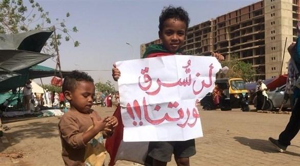 طلف سوداني يحمل لوحة من شعارات المتظاهرين (أ ف ب)