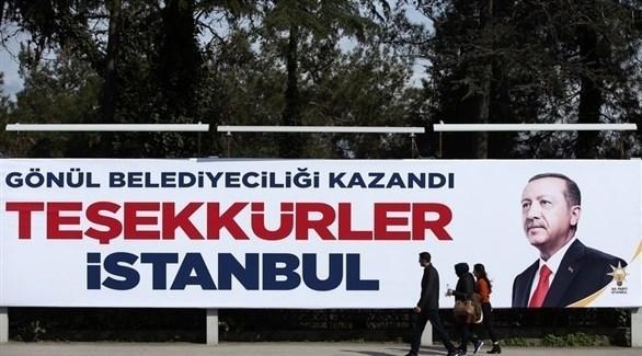 مواطنون أتراك يمرون بجانب لوحة انتخابية تحمل صورة أرودغان بإسطنبول (إ ب أ)