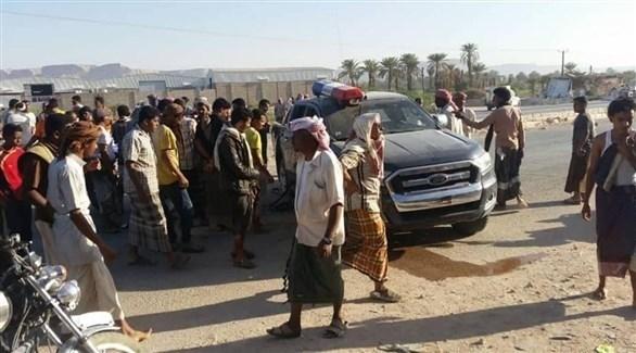 يمنيون حول السيارة المستهدفة بالتفجير اليوم في سيئون بحضرموت (تويتر)