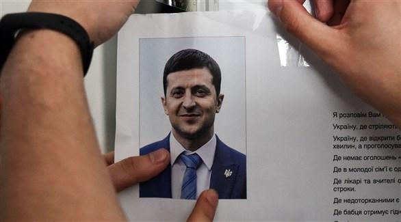 تعليق صورة فولوديمير زيلينسكي داخل مراكز الاقتراع (أ ف ب)