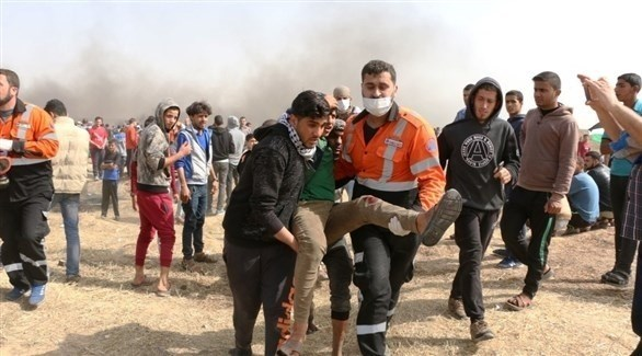 مسعف ومتطوع ينقلان مصاباً في مسيرات العودة بعزة (أرشيف)