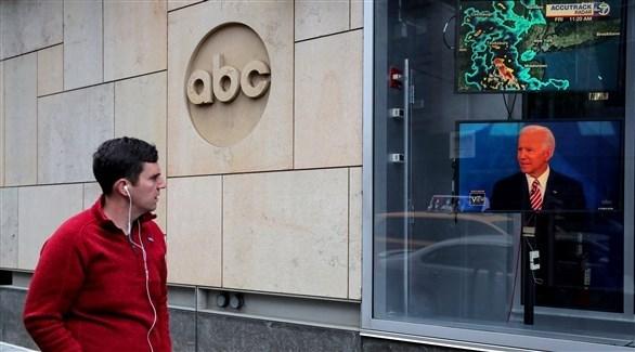 رجل أمام شاشة تلفزيون تعرض مقابلة مع بايدن (رويترز)