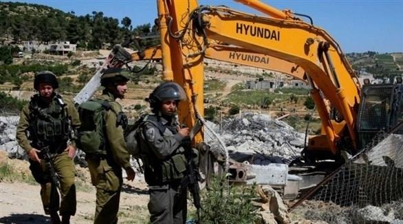 جرافة إسرائيلية تهدم بيتاً فلسطينياً تحت حماية جنود الاحتلال (أرشيف)