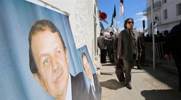 امرأة تمر بجانب صور للرئيس المستقيل بوتفليقة (أرشيف)