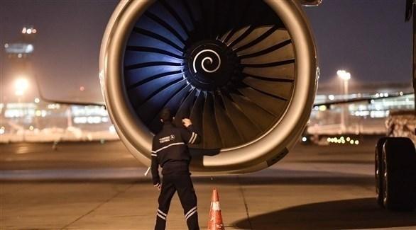 أحد العاملين يقف أمام محركة طائرة (أ ف ب)