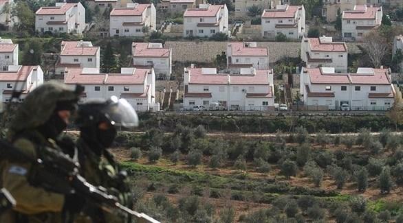 جنديان إسرائيليان يسيران بالقرب من مستوطنة مقامة على الأراضي الفلسطينية (أرشيف)