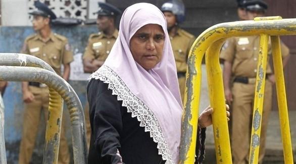 سيدة سريلانكية مسملة تعبر من أمام عدد من العسكريين (أرشيف)
