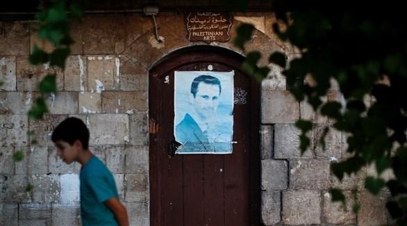 طفل يمر بجانب بوابة عليها صورة للرئيس السوري (أرشي/ أ ب)