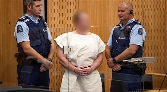 العنصري الأسترالي برينتون تارانت بين شرطيين في محكمة بعد إيقافه (أرشيف)