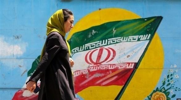 إيرانية أمام صورة للعلم الإيراني (أرشيف)