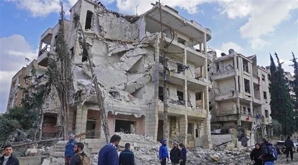 سوريون يتفقدون مبان دمرها القصف في إدلب (أرشيف)