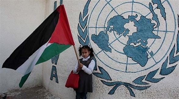 طفلة ترفع العلم الفلسطيني إلى جانب شعار الأمم المتحدة (أرشيف)