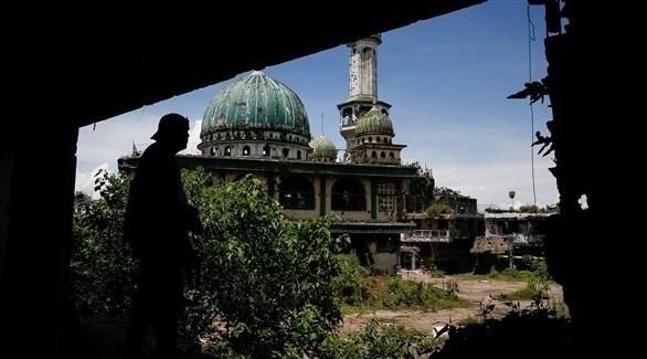 شخص يمر بجانب الأبنية المتصدعة في المراوي الفلبين (اي بي ايه)