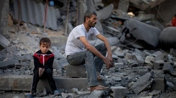 رجل وطفل يجلسان أمام أنقاض منزل مدمر في غزة (أرشيف)