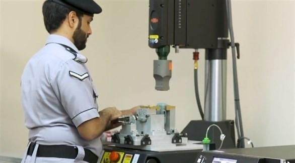 شرطي إماراتي يتفقد جهازاً لتصنيع الأساور الإلكترونية (وام)