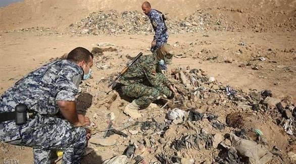 عناصر أمن عراقيون في مقبرة جماعية بالموصل (أرشيف)
