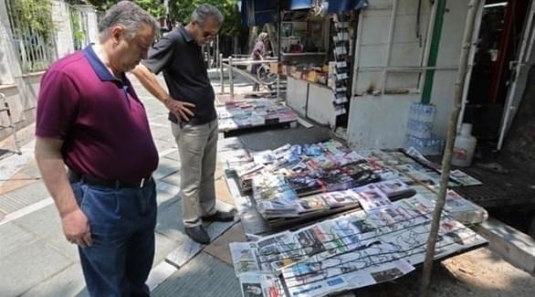 قراء يطالعون مجموعة من الصحف معروضة في شوارع طهران (غيتي)