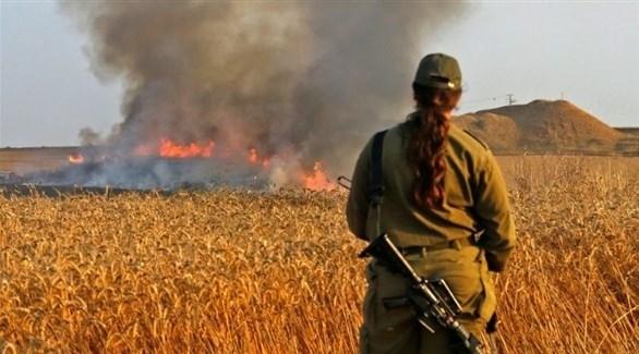 مجندة إسرائيلية تراقب حريقاً في إسرائيل سببه بالون حارق من غزة  (أرشيف)
