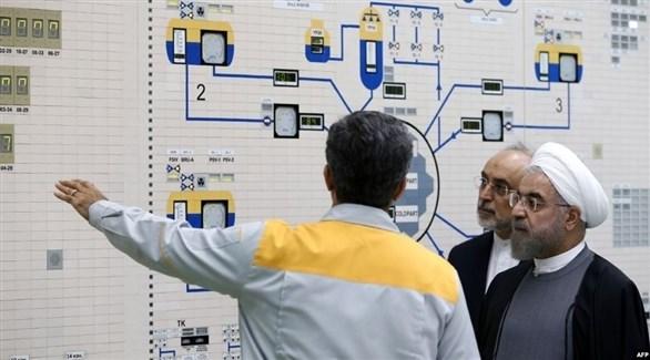 روحاني يستمع لشرح من أحد التقنيين في مفاعل بوشهر النووي (أ ف ب)