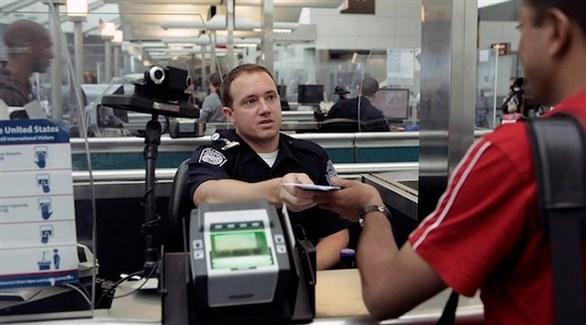 موظف من سلطة الهجرة الأمريكية يعيد جواز سفر إلى سائح قبل دخوله البلاد (أرشيف)