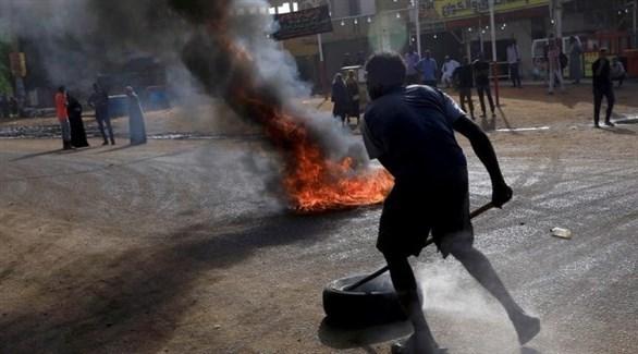 سوداني يدفع إطاراً مطاطياً قريباً من عجلة محترقة في أحد شوارع الخرطوم (أرشيف)