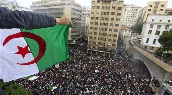 جزائري يرفع علم بلاده فوق ساحة مكتظة بالمحتجين (أرشيف)