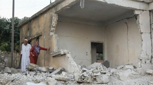 سوريان يتفقدان الدمار غداة قصف جوي لقوات النظام على الأرجح، على بلدة محمبل بمحافظة إدلب (أ ف ب)