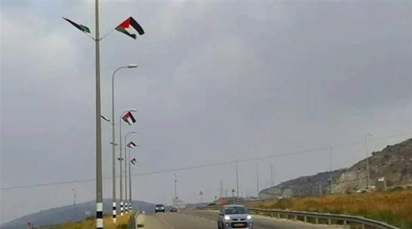 الأعلام الفلسطينية في شارع بمستوطنة في الضفة الغربية (تويتر)