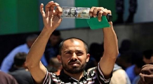 فلسطيني يعرض 100 دولار نصيبه من المساعدة القطرية في غزة (أرشيف)
