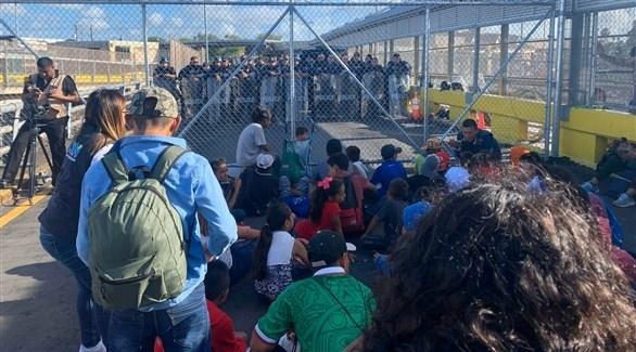 الشرطة بمواجهة المهاجرين عل الجسر (تويتر)