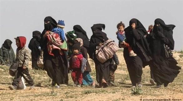 نساء من عائلات داعش مع أطفالهن يغادرون الباغوز السورية (د ب أ)