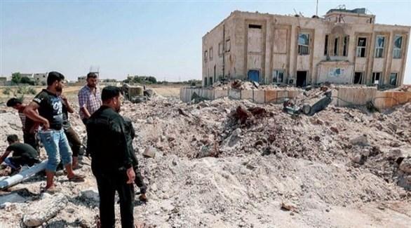 مواطنون سوريون قرب حفرة سببتها غارة روسية على بلدة أورم الكبرى بين حلب وإدلب شمال سوريا (أرشيف)