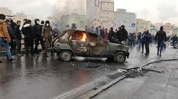 متظاهرون حول سيارة محترقة في أحد شوارع طهران (تويتر)