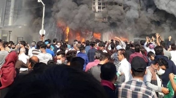إيرانيون أمام مبنى رسمي أتت عليه النيران في الاحتجاجات (تويتر)