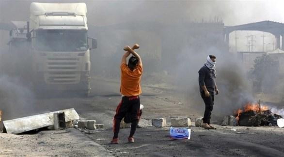 متظاهران عراقيان يقطعان طريقاً أمام شاحنة (أرشيف)