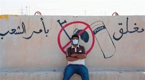 متظاهر عراقي تحت شعار مغلق بأمر الشعب (أرشيف)