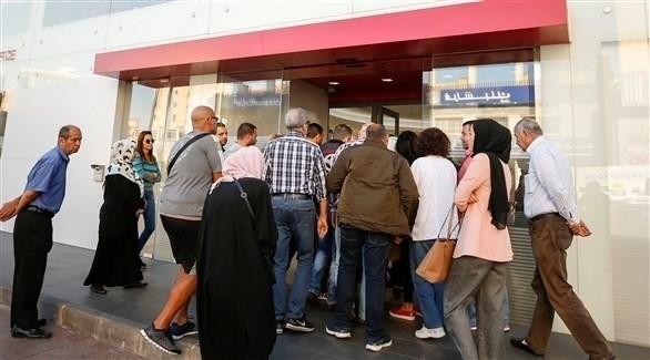 لبنانيون في طابور أمام أحد البنوك (رويترز)