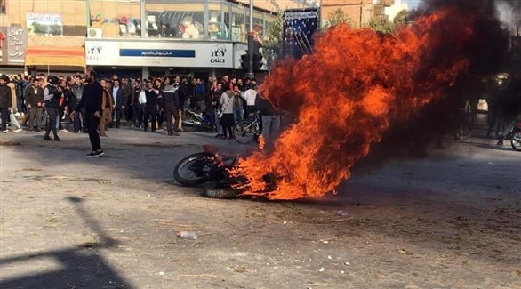 متظاهرون أمام دراجة نارية تحترق في طهران (أرشيف)