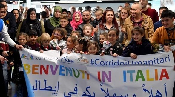 رفع يافطة مرحبة باللاجئين السوريين (أ ف ب)