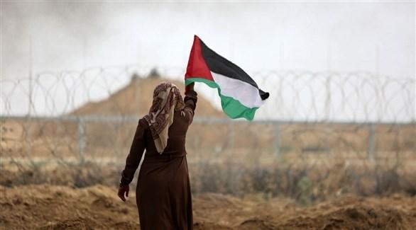 امرأة تحمل العلم الفلسطيني بالقرب من حدود قطاع غزة مع إسرائيل (أرشيف)
