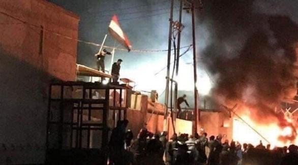 متظاهرون يرفعون العلم العراقي على أحد مداخل القنصلية الإيرانية (تويتر)