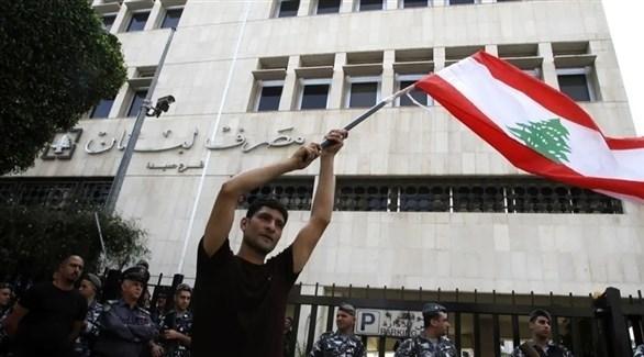 متظاهر لبناني يرفع علم بلاده أمام مصرف لبنان (أرشيف)