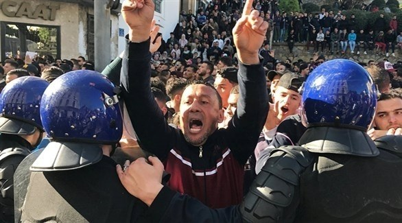 عناصر من الشرطة تقف أمام تجمهر للمتظاهرين في الجزائر (أرشيف)