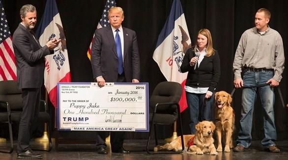 الرئيس الأمريكي دونالد ترامب يمسك شيكاً باسم مؤسسته الخيرية (أرشيف)