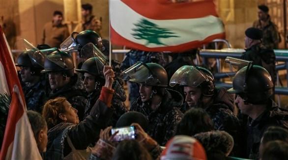 متظاهرون يقفون أمام رجال أمن في وسط بيروت (اي بي ايه)