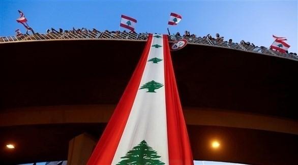 متظاهرون يرفعون العلم اللبناني على جسر جل الديب شمالي بيروت (أرشيف / رويترز)